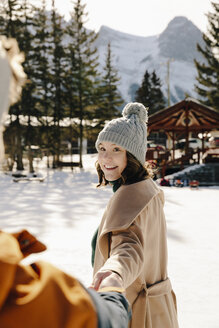 Smiling young woman holding boyfriend's hand in snow - HEROF36253