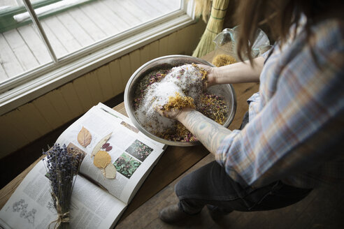 Female business owner mixing herbs and dried flowers in apothecary - HEROF36303