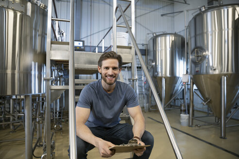 Portrait confident male brewer working in brewhouse distillery - HEROF36321