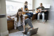 Mother working from home while children practice guitar in background - HEROF36333