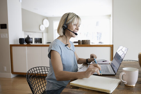 Smiling mature woman working from home, using headset at laptop - HEROF36360