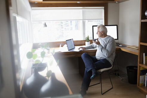Senior man working at home, using laptop in home office - HEROF36384
