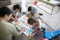 Family coloring birthday sign on floor - HEROF36498