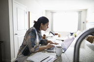 Woman working from home at laptop in kitchen - HEROF36504
