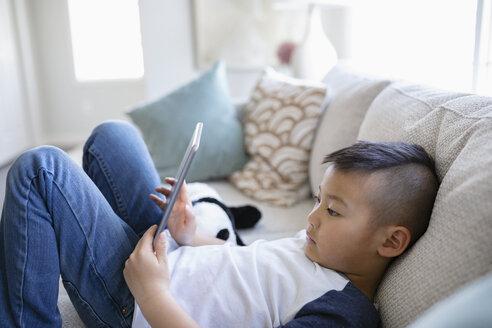 Boy using digital tablet on living room sofa - HEROF36507