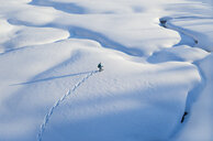 Drone point of view woman cross country skiing across snow covered landscape, Alberta, Canada - HEROF36513