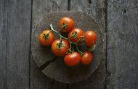 Tomatoes on vine on wooden tree slice - BLEF03246