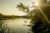 Distant Mari man fishing on lake, Ural, Russia - BLEF03252