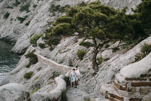 Caucasian couple hiking on cliff near lake - BLEF03264