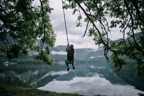Caucasian woman swinging on rope swing at lake - BLEF03267