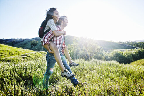 Smiling Man carrying girlfriend piggyback on hill - BLEF03309