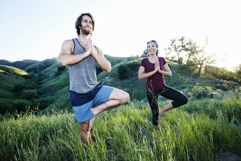 Smiling couple practicing yoga on hill - BLEF03312