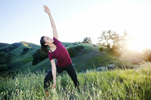 Mixed Race woman practicing yoga on hill - BLEF03315