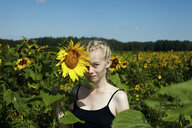Caucasian girl holding sunflower - BLEF03381