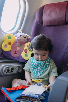 Toddler girl sitting on airplane watching picture book - GEMF02950