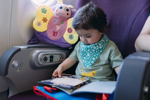 Toddler girl sitting on airplane watching picture book - GEMF02953