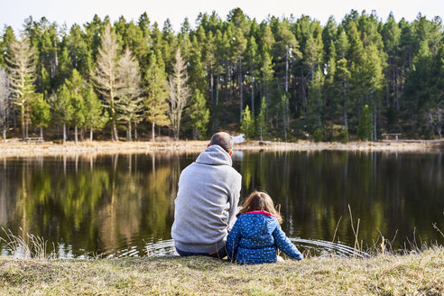 France, Pyrenees, back view of father and little daughter sitting side by side in front a lake - GEMF02959