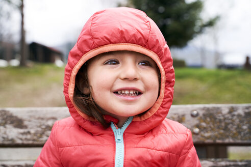 Portrait of happy toddler girl wearing red down jacket with hood - GEMF02962