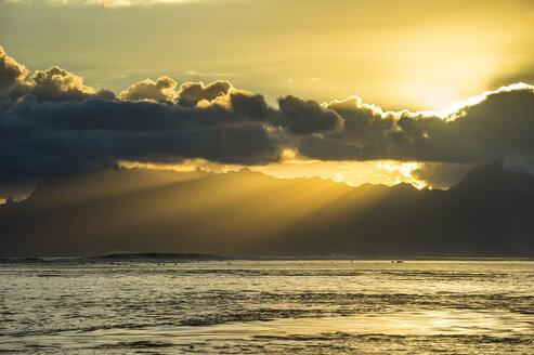French Polynesia, Tahiti, sunrays breaking through the clouds over Moorea - RUNF02070