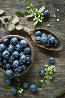 Bowl of blueberries, wooden spoon, blueberry blossoms on wood - ASF06411