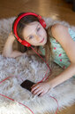 Girl lying on carpet at home listening to music with headphones and smartphone - SARF04281