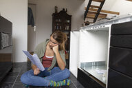 Frustrated young woman reading assembly instructions in kitchen - GUSF01968