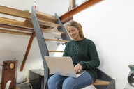 Smiling young woman sitting on stairs at home using laptop - GUSF01974