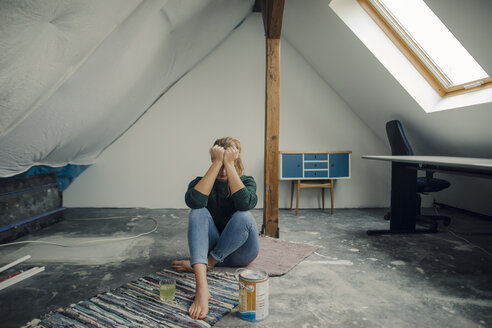 Frustrated young woman sitting on the floor in attic with paint bucket - GUSF01980