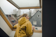 Smiling young woman in raincoat looking out of attic window - GUSF01989