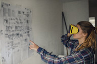 Young woman wearing VR glasses with assembly instructions at the wall - GUSF01995