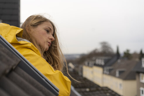 Pensive young woman in raincoat leaning out of roof window - GUSF02013