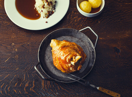 Crispy roasted pork knuckle. Schweinshaxe, roasted ham hock in a pan on wooden table - PPXF00194