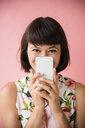 Hispanic woman hiding face behind cell phone - BLEF03429