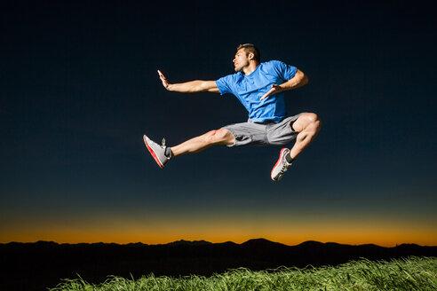 Caucasian man jumping at sunset - BLEF03477