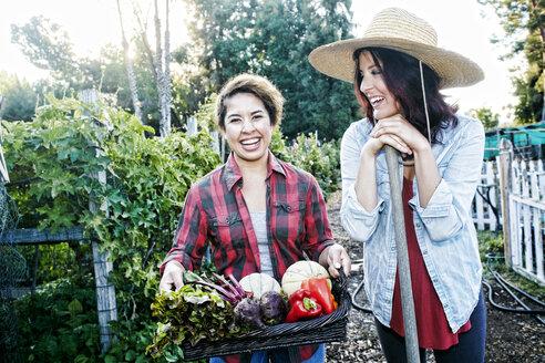 Portrait of women with basket of vegetables in garden - BLEF03504