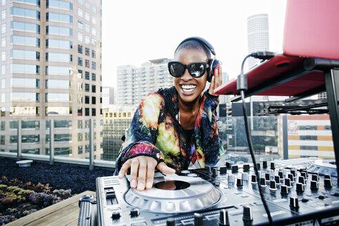 Smiling Black DJ on urban rooftop - BLEF03507