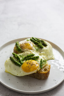 Slices of baguette garnished with fried eggs and Asparagus on a plate - GIOF06327
