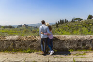 Young couple embracing at wall in Florence, Tuscany, Italy - MGIF00436