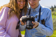 Couple looking at pictures on their digital camera - MGIF00439