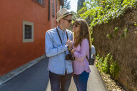 Affectionate couple strolling through narrow alleys in Florence, Tuscany, Italy - MGIF00445