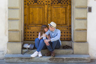 Young couple sitting on stairs, taking a break on a city trip - MGIF00448