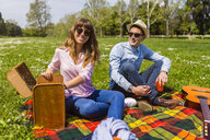 Young couple having a picnic with healthy food in a park - MGIF00451