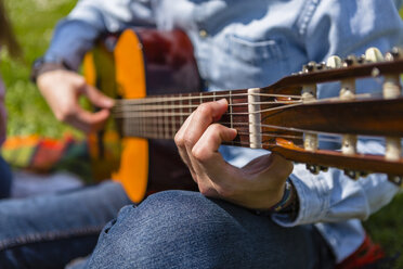 Young man playing the guitar in a park - MGIF00460