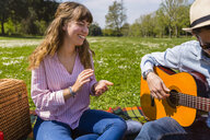 Young man playing the guitar for his girlfriend in a park - MGIF00463