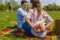 Young woman gifting her boyfriend with a present in a park - MGIF00466