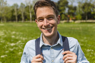 Smiling young man in a park, portrait - MGIF00478