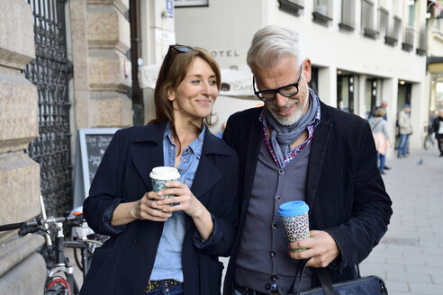 Smiling mature couple with reusable bamboo cups in the city - ECPF00740
