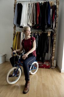 Woman sitting on children's bike at home - FLLF00150