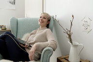 Happy woman sitting in armchair at home with tablet - FLLF00156