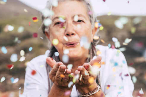 Senior woman blowing confetti outdoors - SIPF01976